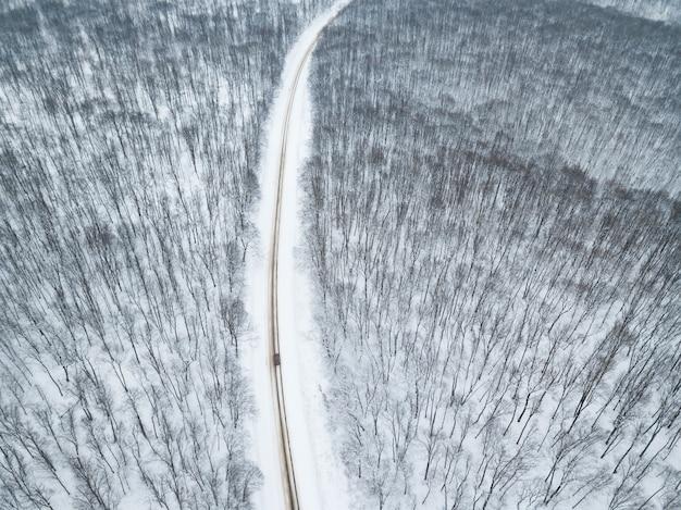 숲과 도로 위에 눈이 내리는 놀라운 겨울 풍경 위의 무인 항공기에서 아름다운 경치 사진
