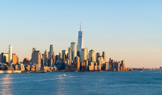 アメリカのハドソン川に架かるニュージャージー州ホーボーケンからのニューヨーク市のダウンタウン、マンハッタンの美しい風光明媚な夕景。アメリカの有名な魅力と象徴的な青いスカイラインビュー。