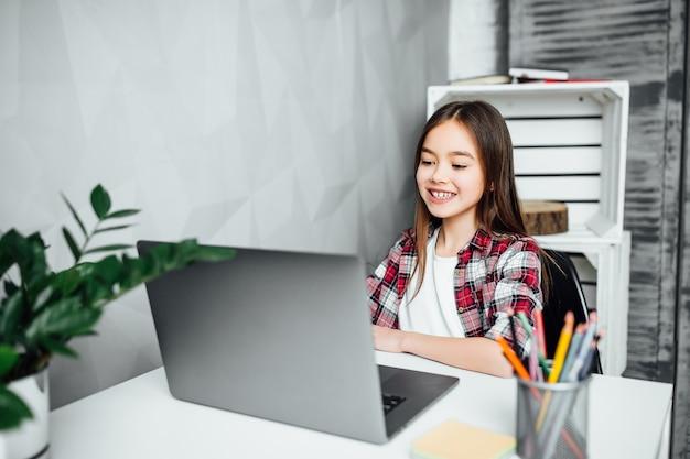 自由時間に自宅で宿題をしている美しい女子高生