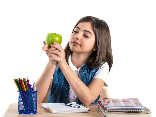 A beautiful school girl sits at the desk with apple and thinking. white background.