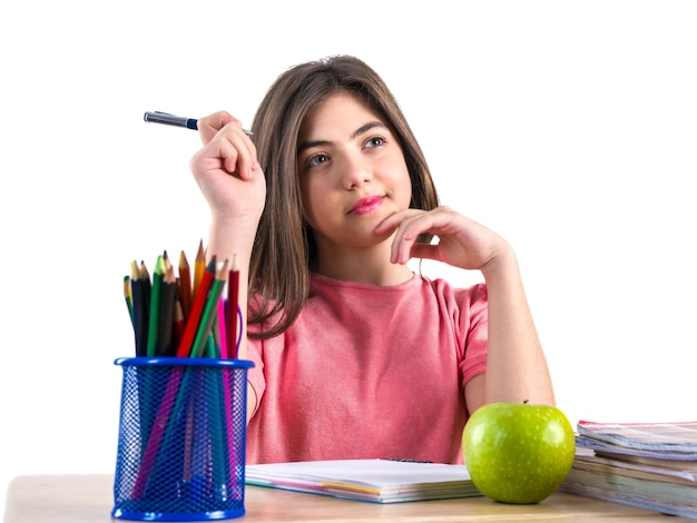 A beautiful school girl sits at the desk with apple and thinking white