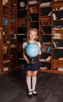 Beautiful school girl in uniform with a globe in the library
