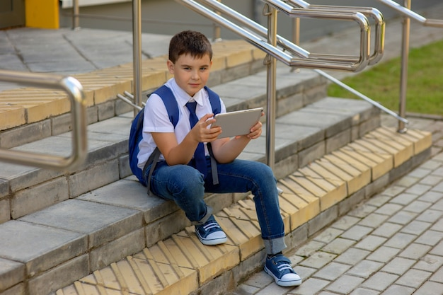 A beautiful schoolboy in a white shirt with a blue backpack, blue tie, blue jeans sits on the stairs outside and plays with a gray tablet.