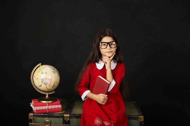A beautiful schoolgirl in a red dress reading a book on a black background while sitting on a chest
