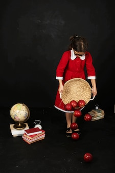 A beautiful schoolgirl in a red dress with a books apples and globe on a black background