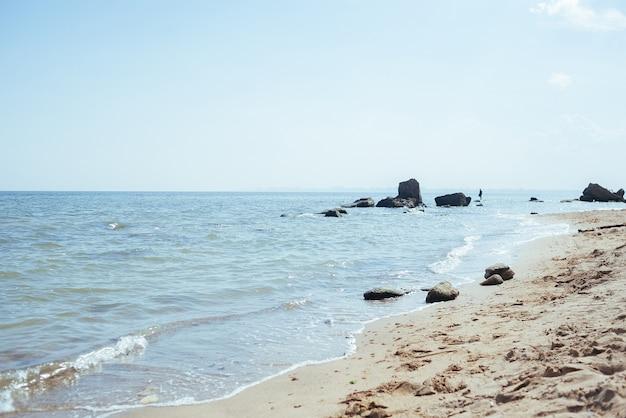 여름에는 정오에 아름다운 바다, 맑은 물, 모래 해변. 조용한 파도는 한낮의 태양에 의해 비춰집니다.