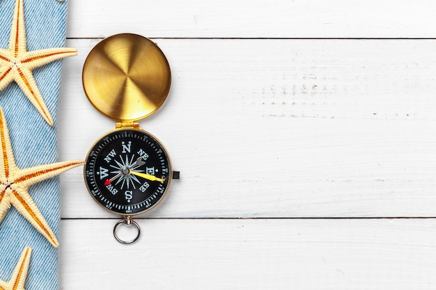 Beautiful sea composition with shells and vintage compass on white wooden background