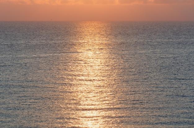 水面に太陽が反射する美しい海の日の出。