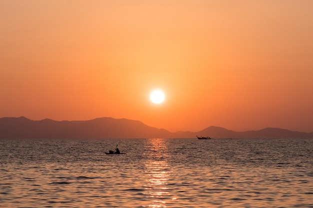 Beautiful sea sunset with silhouettes of fishing boats against the rocky coast