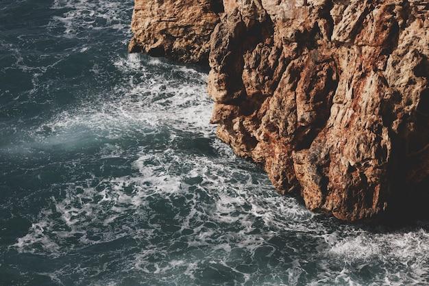 美しい海の波と岩だらけ