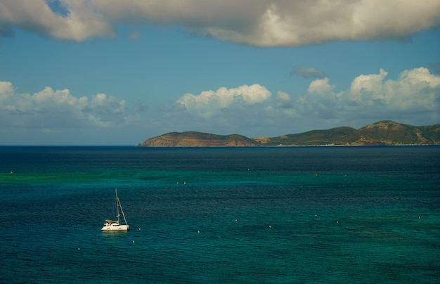 Красивое море с парусными лодками, яхтой и небольшим островом на фоне.