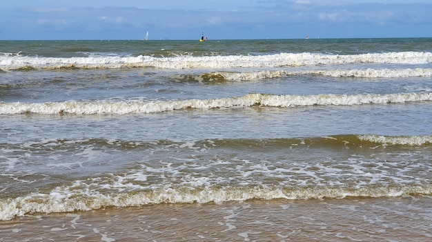 砂、ヨット、水面の波と青い空の美しい海。夏休みの自然な背景。