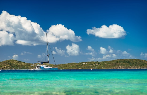 Красивое море с яхтой и островом на фоне.