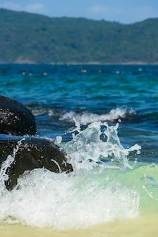Красивый морской пейзаж. волна разбивается о камни и брызги воды разлетаются.
