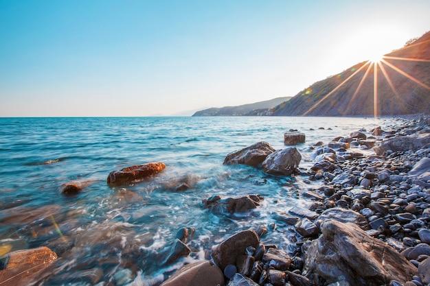 따뜻하고 화창한 여름 아침에 높은 산과 언덕을 배경으로 바위 해변을 따라 파도가 튀는 아름다운 바다 경치. 여행 개념. 광고 공간