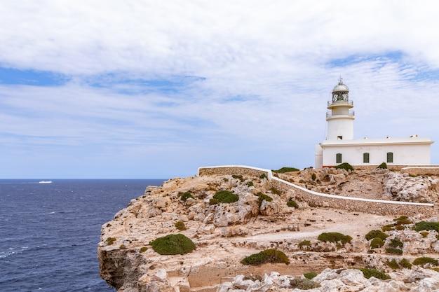 Красивый морской пейзаж с маяком на скале и круизным лайнером в море. менорка, балеарские острова, испания