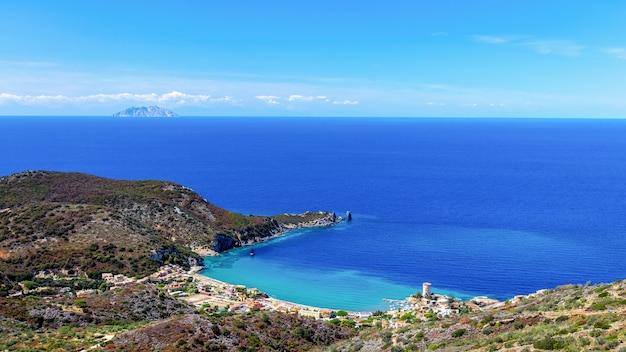 Красивый морской пейзаж с пляжем и прибрежным городком с маяком в бухте острова джильо