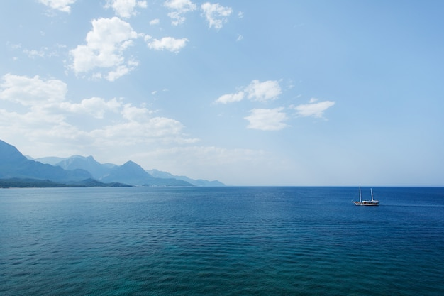 Beautiful seascape with sea, clouds, mountains and yacht