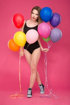 Beautiful seductive attractive young lady in black leotard and sneakers posing with colorful balloons on pink wall