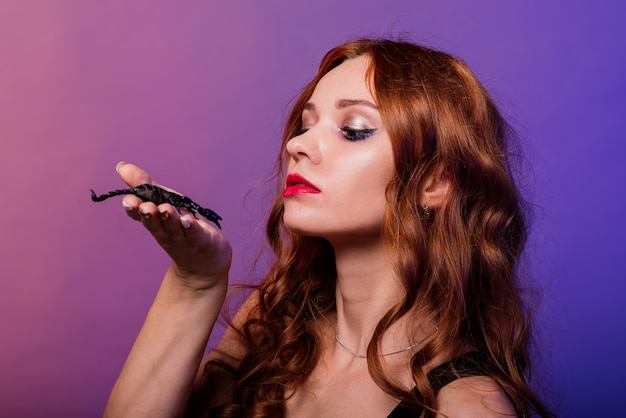 Beautiful seductive fashion redhead female with make up with a scorpion in studio