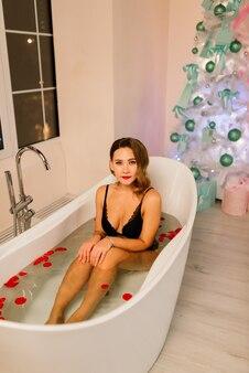 긴 머리를 가진 속옷에 아름다운 매혹적인 여성은 목욕, 크리스마스 트리 걸립니다