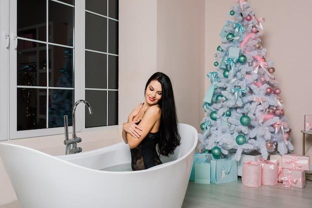 긴 머리를 가진 속옷을 입은 아름다운 매혹적인 여성이 목욕을 하고, 크리스마스 트리를