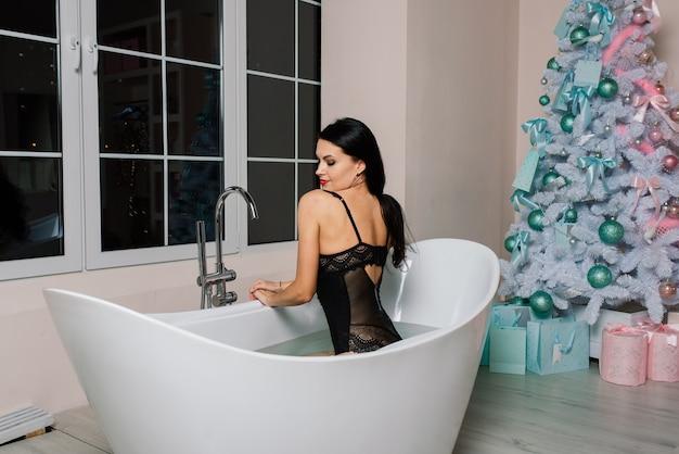 긴 머리를 가진 속옷을 입은 아름다운 매혹적인 여성이 목욕, 크리스마스 트리를 가져옵니다.