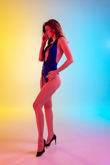Beautiful seductive girl in fashionable blue swimsuit on bright gradient yellow-blue in neon light