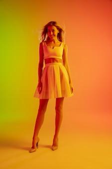 Bella ragazza seducente in abito alla moda e romantico su sfondo verde-arancio sfumato luminoso in luce al neon.