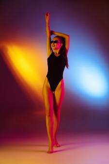 Bella ragazza seducente in costume da bagno alla moda su sfondo bicolore da discoteca al neon in neon