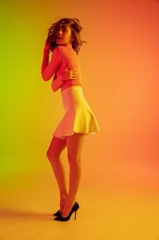 Красивая соблазнительная девушка в модном, романтическом наряде на ярком градиентном зелено-оранжевом фоне в неоновом свете. портрет в полный рост. copyspace для рекламы. лето, мода, красота, концепция эмоций.