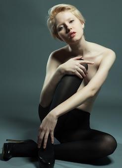 黒のパンストを着てファッション ポーズで座っている美しく魅惑的な女性