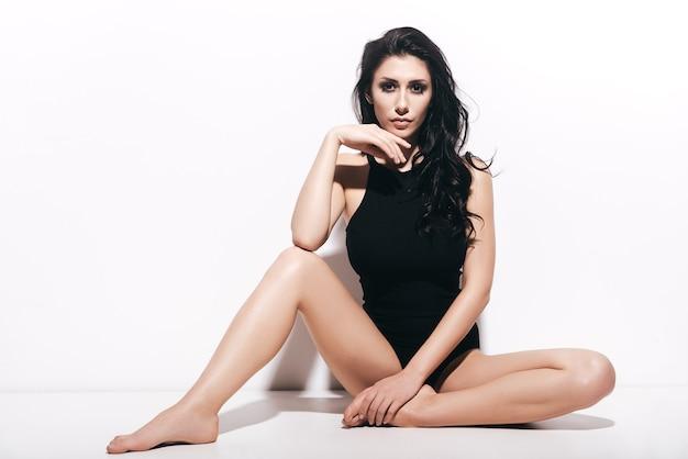 아름다운 유혹자. 흰색 배경 앞에 앉아있는 동안 카메라를보고 검은 수영복에 매력적인 젊은 여자