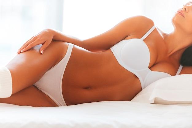 Красивая соблазнительница. обрезанное изображение красивой молодой женщины в нижнем белье и белых носках, лежа в постели