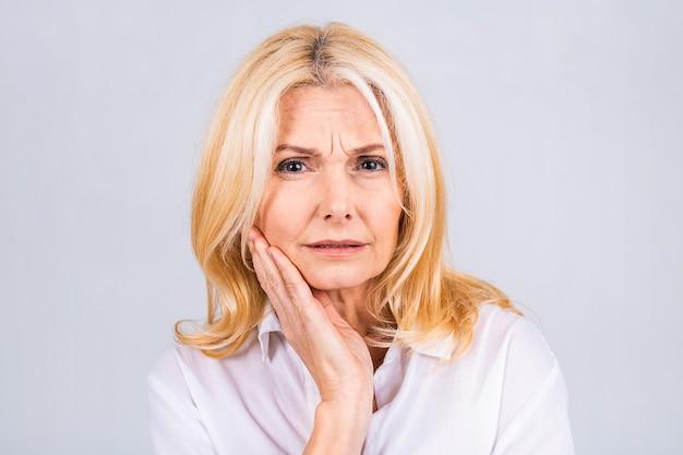 치아에 치통이나 치과 질환 때문에 고통스러운 표정으로 손으로 입을 만지는 아름다운 중년 여성. 치과 개념입니다.