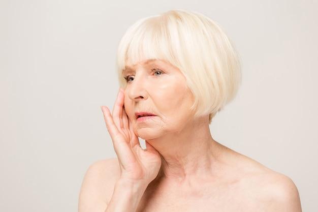 歯痛や歯の歯の病気のために痛みを伴う表情で手で口に触れる美しい年配の女性。歯科医の概念。