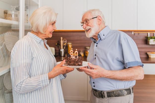 Beautiful senior couple celebrating  anniversary with birthday cake - elderly couple having birthday party at home