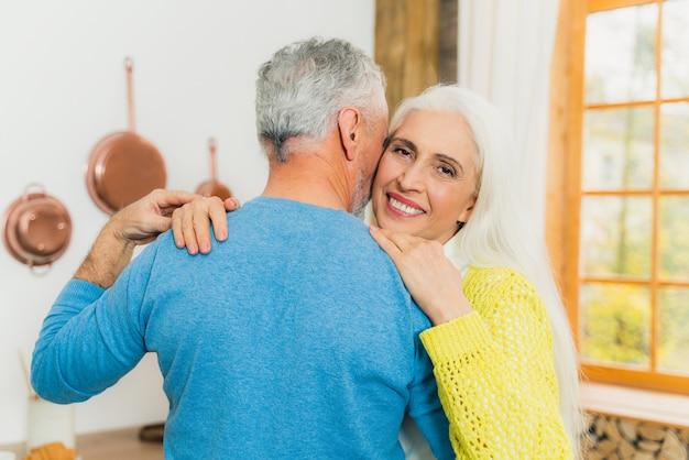 Beautiful senior couple dancing at home.