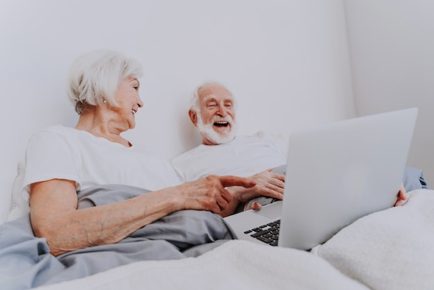 Beautiful senior couple enjoying time together at home - moder elderly couple surfing the internet on laptop computer