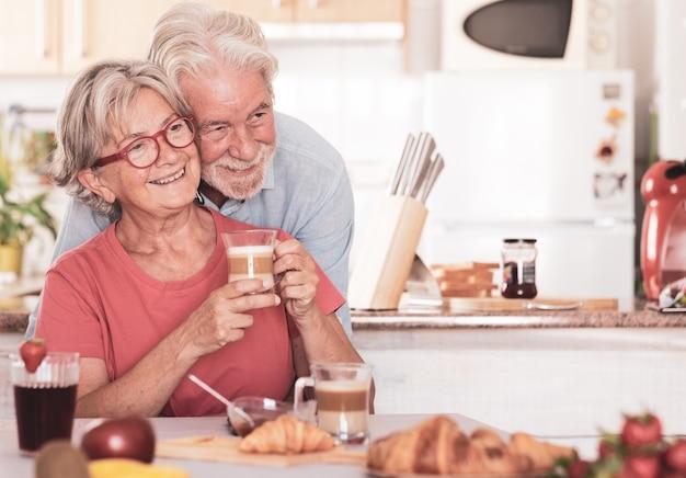Красивая пара старших за завтраком дома. пенсионеры счастливые люди пьют капучино, едят фрукты и круассан