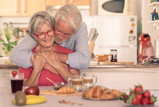 Красивая старшая пара завтракает дома, начиная с утра с теплых объятий. горячий круассан с капучино на столе