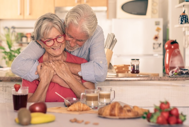 Beautiful senior couple having breakfast at home, starting morning with a warm hug. hot cappuccino croissant on the table