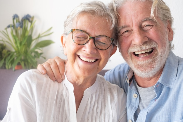 은퇴를 즐기는 소파에 앉아 재미와 웃는 아름다운 노부부
