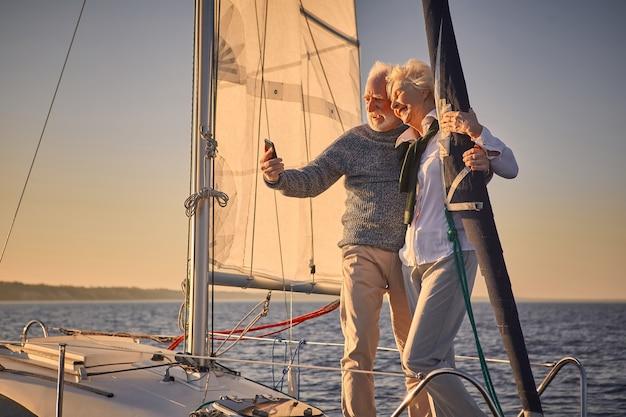彼らが立っているスマートフォンで自分撮りをしながら抱きしめて笑っている美しい年配のカップル