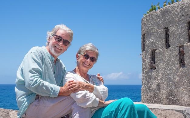 카메라를 보며 여름 휴가를 즐기는 바다에서 껴안고 있는 아름다운 노부부
