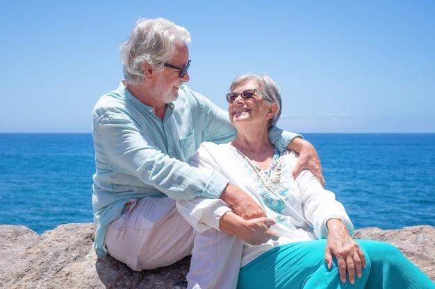 햇빛을 즐기는 바다에서 포옹하는 아름다운 노부부 서로를 바라보는 은퇴한 두 사람