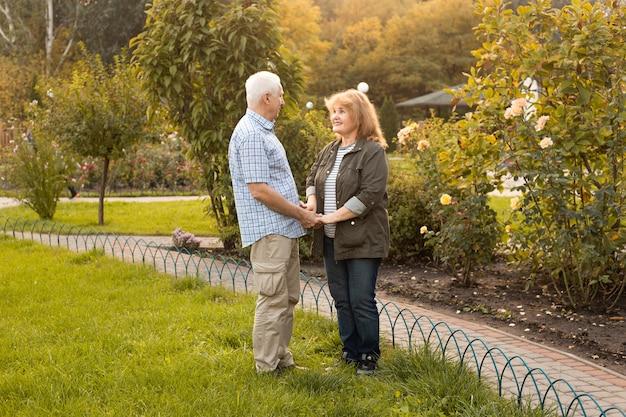 春や夏の自然の中で外で恋をしている美しい年配のカップル