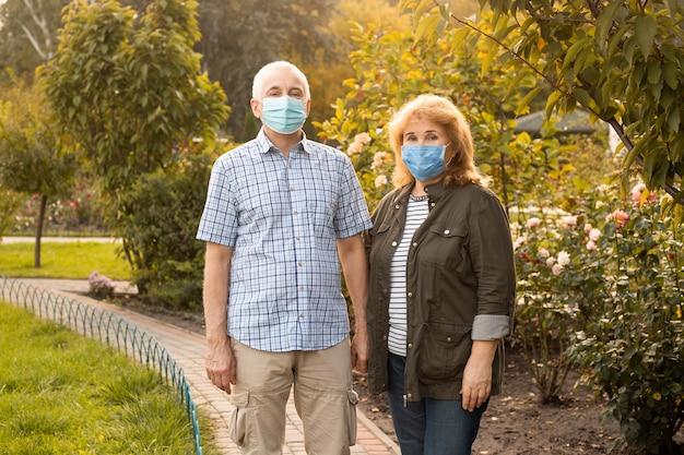 医療マスクを身に着けている愛の美しい年配のカップル