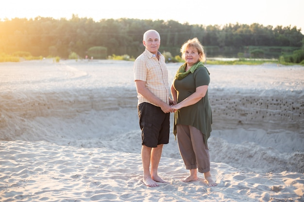 Beautiful senior couple in love outside in beach in summer nature