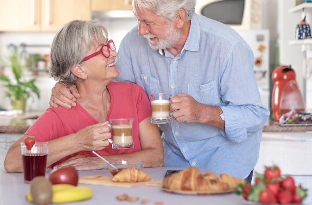 Красивая пара старших улыбается за завтраком дома. пенсионеры счастливые люди пьют капучино, едят фрукты и круассан